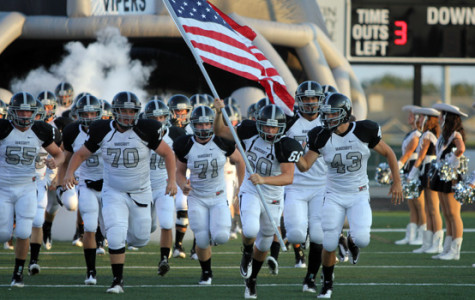Senior Josh Holland, carrying the flag, leads the team onto Nelson Field. Each week, the team captains vote on a player who has been the hardest worker with the best attitude  to carry the flag.