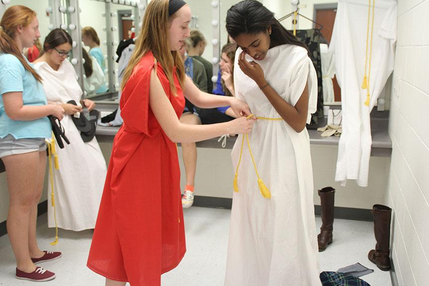 Rachel Frith helps Christina Eure secure her costume before the dress rehearsal of The Greek Mythology Olympiaganza, which opens tonight.