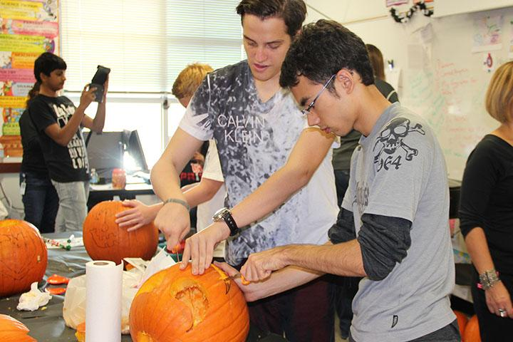 Derya+Yilmaz+and+Yuro+Sato+carve+a+pumpkin+during+the+ESL+cultural+celebration.+