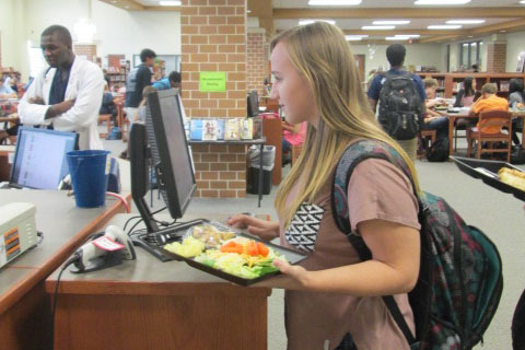 Junior Katie Buschang signs into the library during lunch.