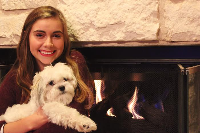 Lauren cozies up with her puppy, Murphy by the fireplace in her home where she will celebrate Thanksgiving with her family.