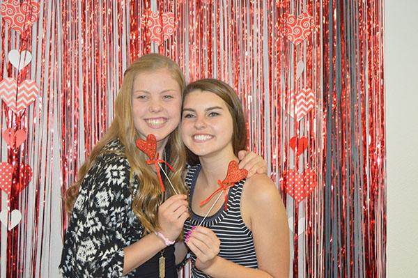 Kendall Shields and Rachel Honts are all smiles for the Valentines-themed photo booth.