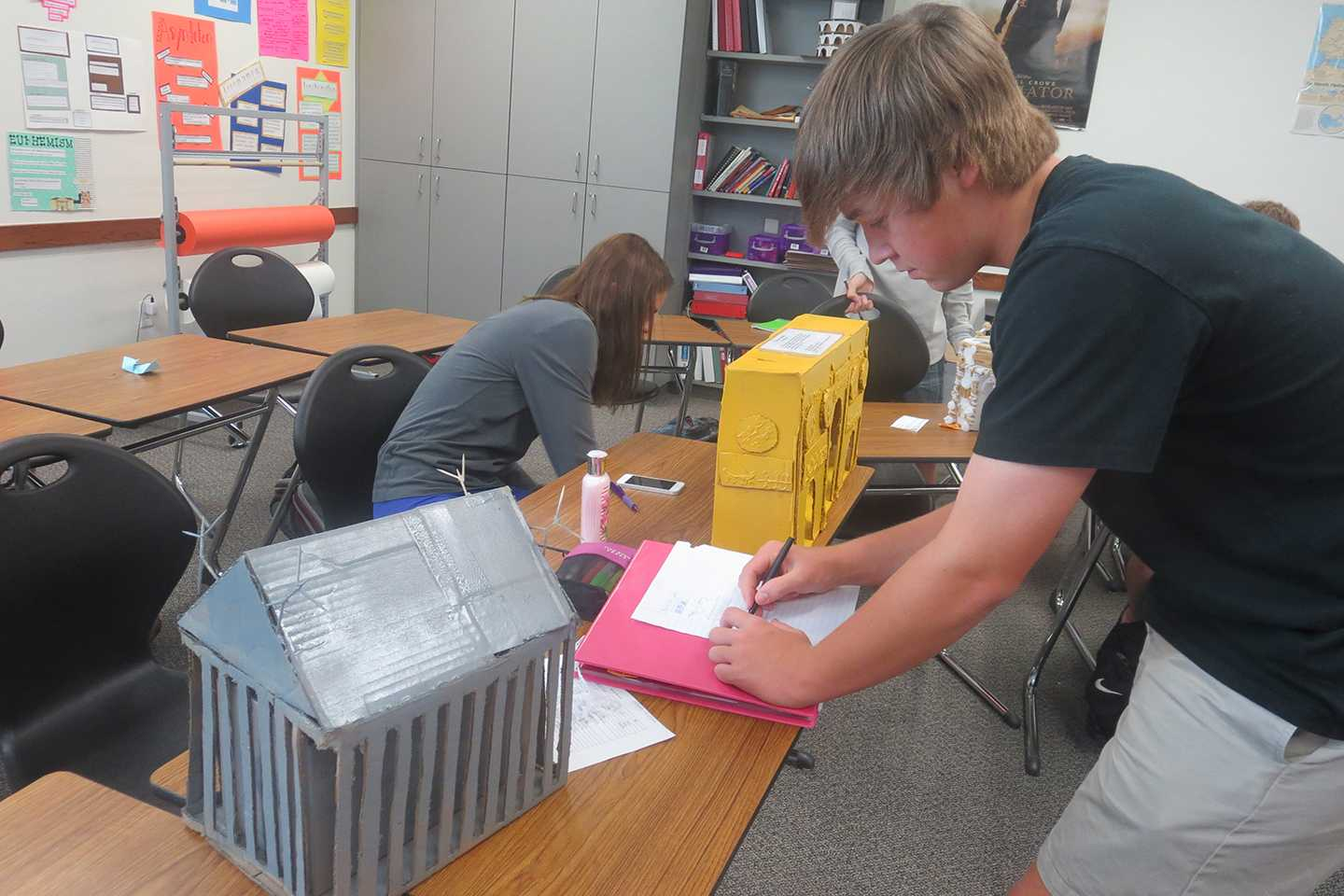 Sophomore Latin student Christopher McKenzie draws another student's project.