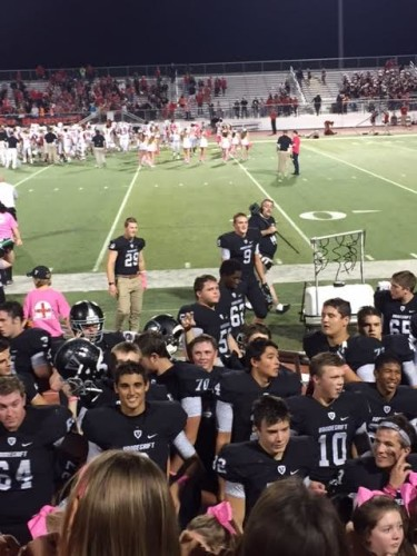 The varsity football team celebrates their 63-55 win against Vista Ridge with the student section.