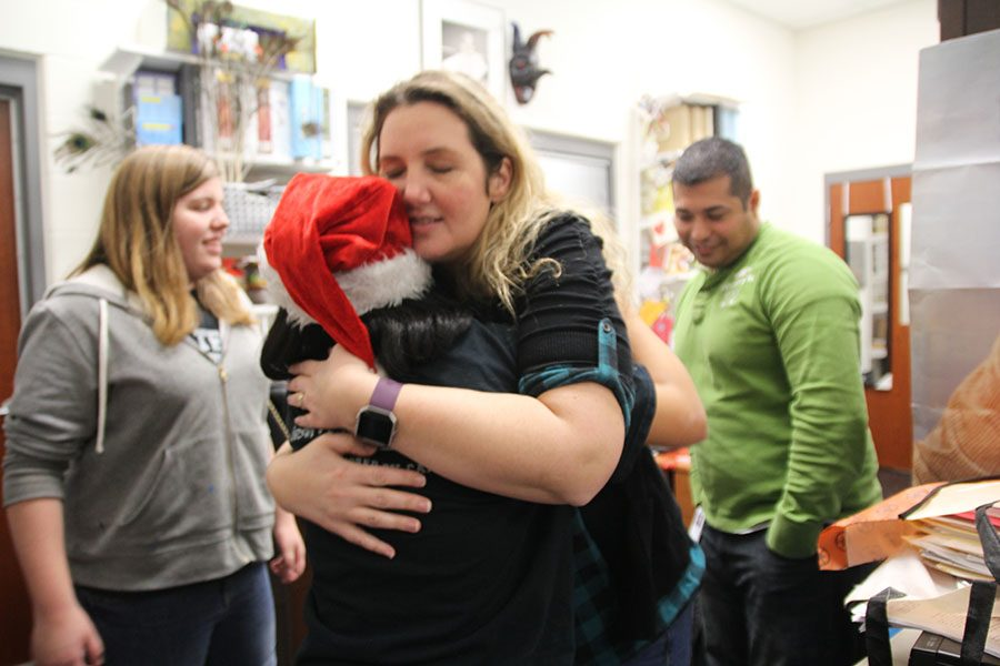 Teacher Nikki Guckian hugs an AD Team member as she was given the poinsettia.