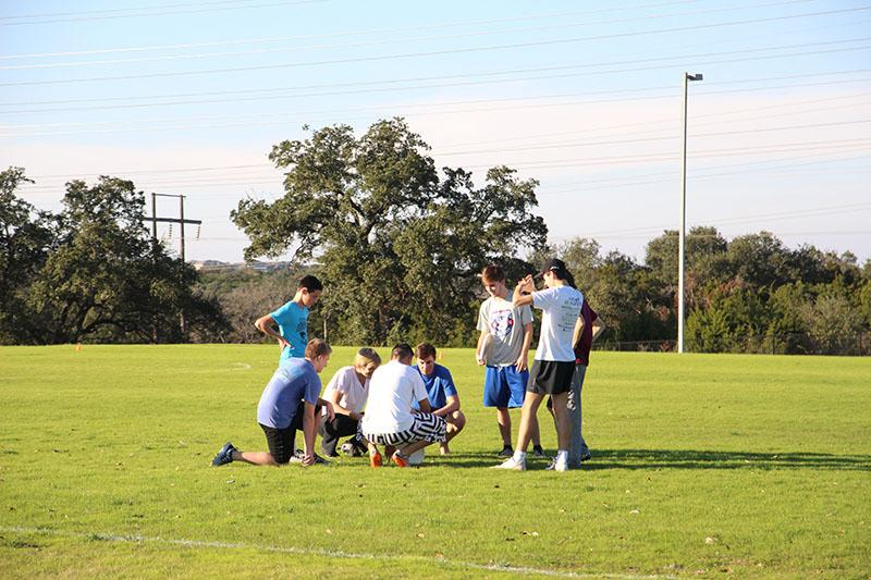 The ultimate frisbee team confers with their coach during practice.