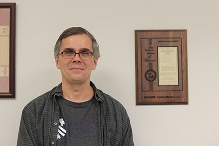 Martin Wiedenmeier standing next to his patent. Wiedenmeier patented his idea for testing heart valves back when he was a biomedical engineer.