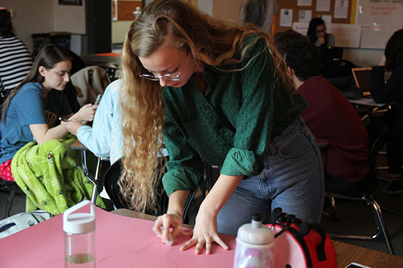 Senior Hannah Barnard works on a poster during a Women's Rights Club Meeting. The club started this school year. Natalie Brink photo