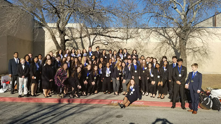 DECA competitors pose for a photo together after district.