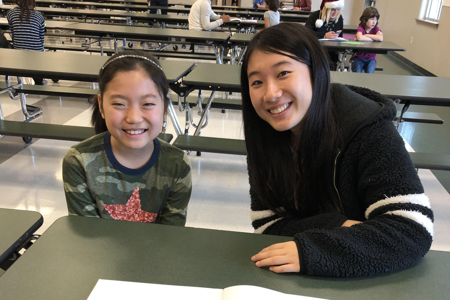 Sophomore Aoi Nishimara reads her story to EL elementary student.