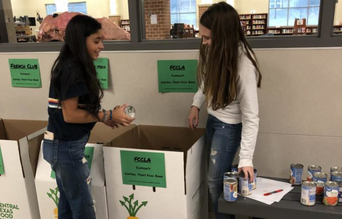 Students+donate+to+the+FCCLA+canned+food+drive+box.
