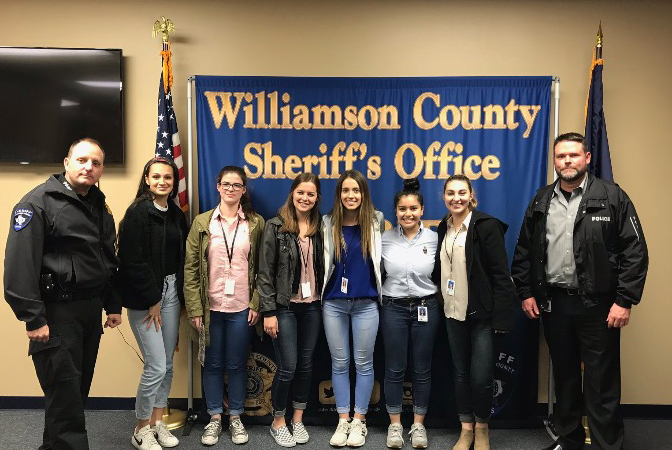 Senior Alexandra Spears takes a group picture with other COOL Week students and officers from the Jonestown Police Department.
