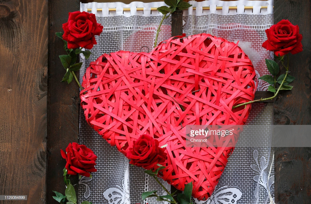 PARIS, FRANCE - FEBRUARY 13: A red heart  and red roses are displayed in the window of a restaurant on the eve of the Valentine's Day on February 13, 2019 in Paris, France. Valentine's Day is a celebration of love and romance for many people across the world. (Photo by Chesnot/Getty Images)