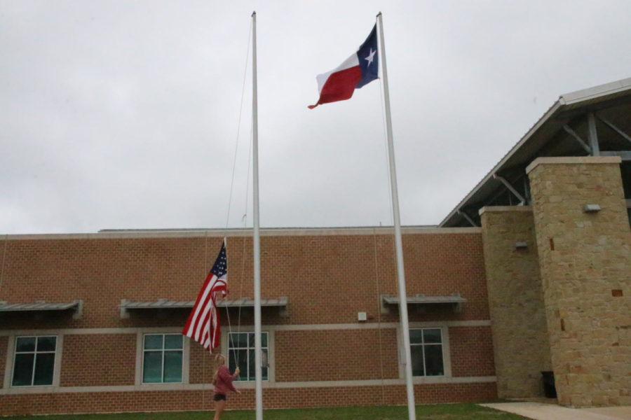 """Senior Sonya McCann raises the flags during fifth block as one of the many jobs the front office aides have. """"Me and Keaton Field have gotten it down to a science and we're able to do it in 2 minutes, but I've learned to do it on my own because Keaton hasn't been here,"""" McCann said."""