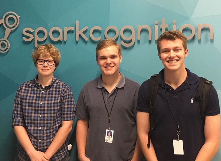 Senior Landon Palmer (far right) standing in front of Sparkcognition's logo with other students participating in LISD's COOL week.