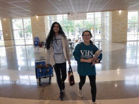 Journalism competitors Harshita Avirneni (left) and Jennifer Walker (right) walk through the school while at another meet.