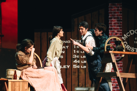Maggie McDonald, played by alternate Anna Zavelson (9), protects Belinda McDonald, played by alternate Sixtine Ronchi (12), as her father, Black McDonald, played by Francis Kim (12), goes after her in a moment of rage. Dr. Jack, played by Carlos Alvarez-Roth (12) attempts to keep him off.