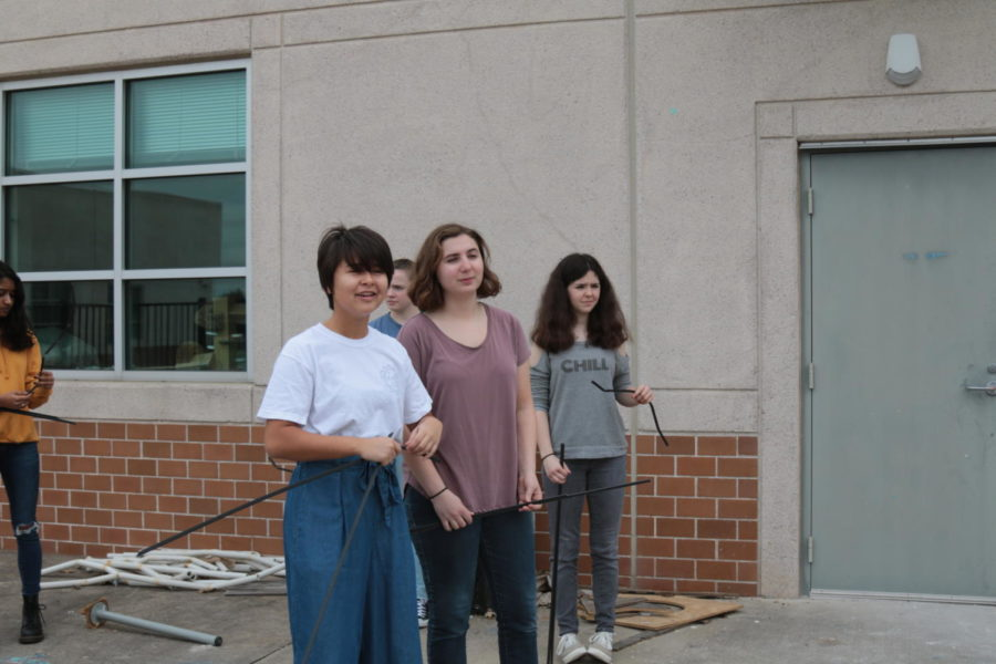 Junior Julia Krupp and senior Megan Gordon use PVC pipes and branches to work on Art Club's Earth Day project during PIT.