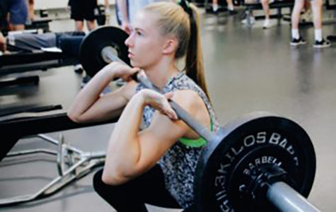 Senior Ina Edstrom lifts weights in the weight room during practice.
