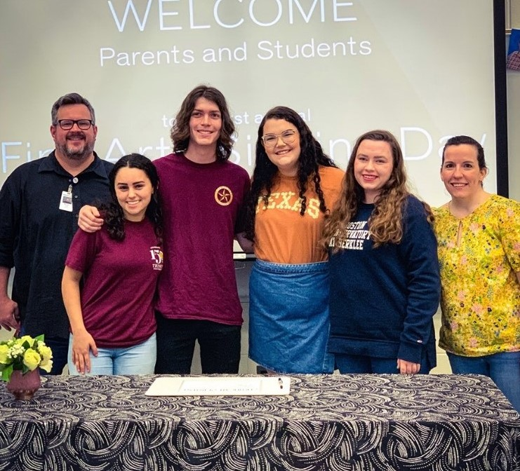Seniors stand with choir directors Michael Zook (left) and Megan Goodman (right) on  the fine arts signing day.