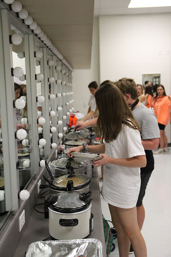"Students line up in the dressing room to get dinner. Almost every student brough crock pots filled with food so the entire cast and crew could eat a full meal during rehearsal. Schneider named the rehearsal the ""crock pot rehearsal"" for that reason."