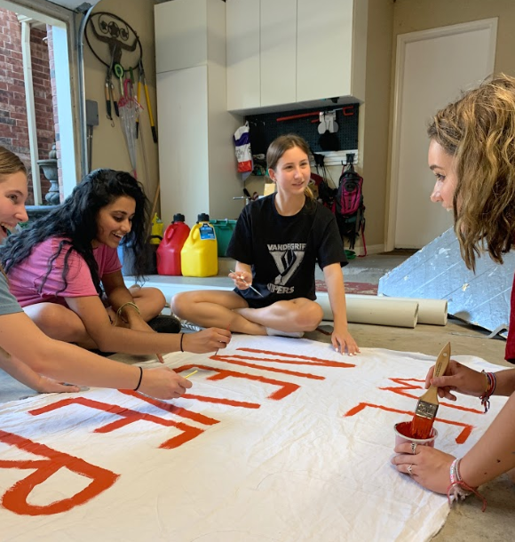 FCCLA+officers+Megan+Henry%2C+Harshita+Avirneni%2C+Elise+Cuellar+and+Anatalia+Felicita+Beiler+joke+around+while+painting+a+banner+for+their+float.