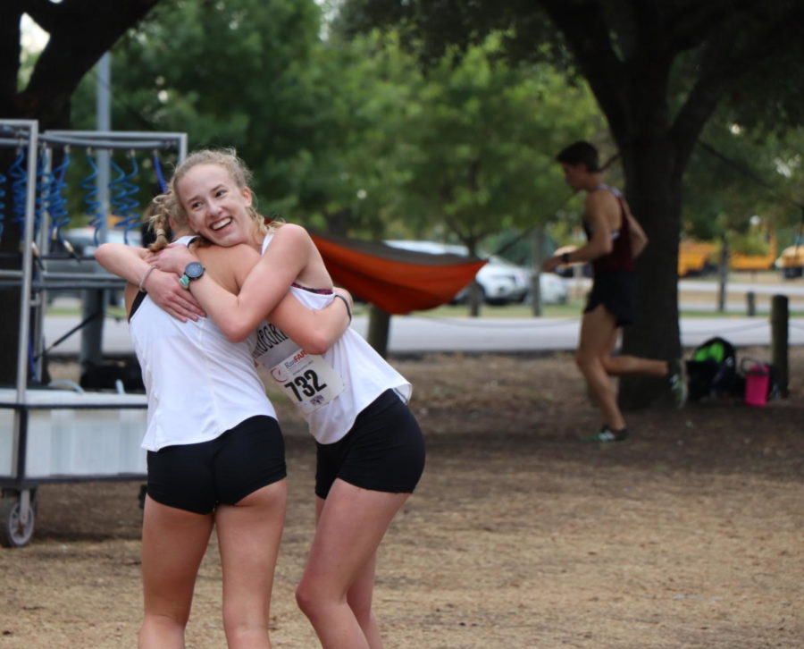 Junior varsity runner Sophia Peterson hugs her teammate after her win.