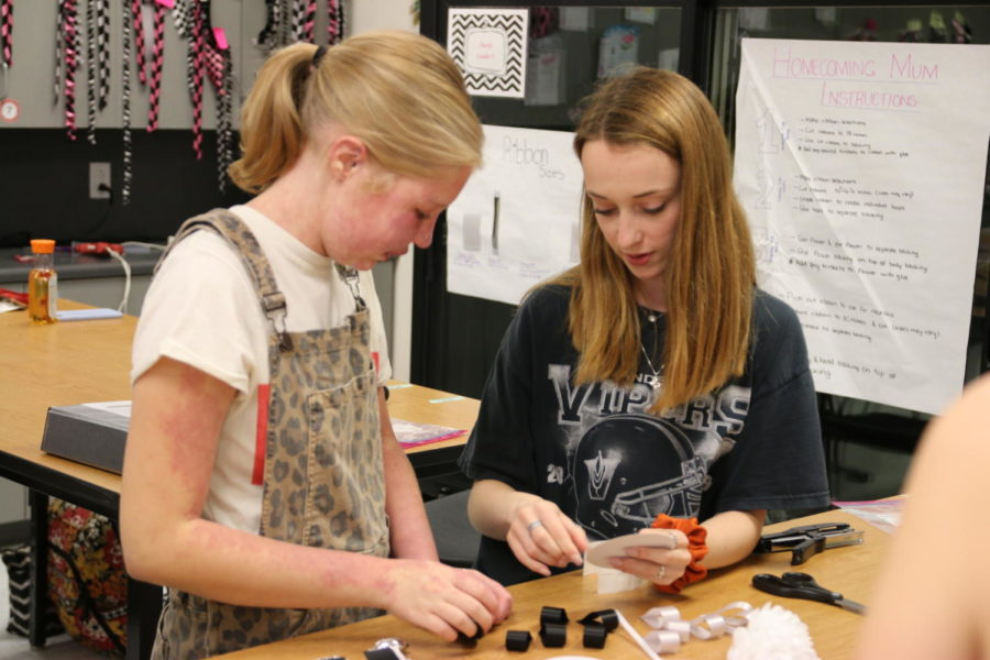 Anna Schulte and Madeline Rawlings work together to create a mum in the floral design lab.