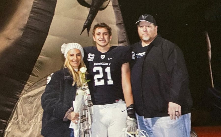 Jax Mccauley (middle) poses with his parents during senior night.