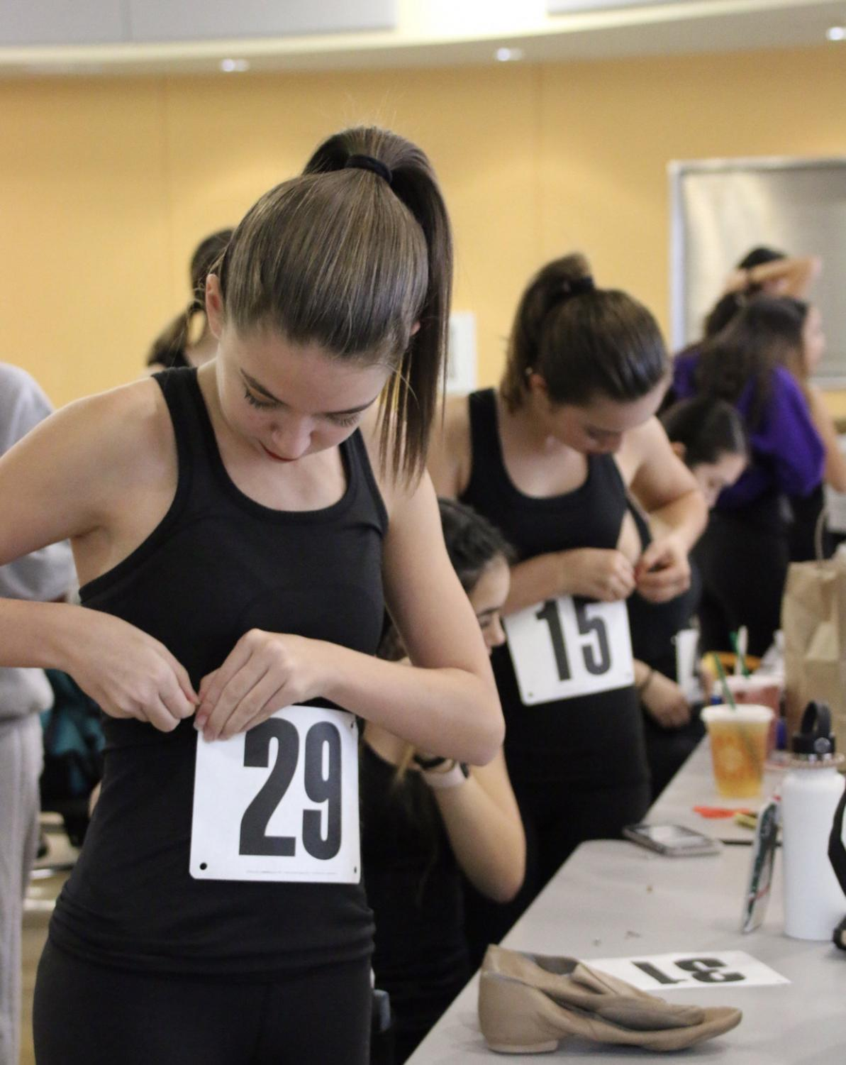 Contestants fasten their contestant numbers