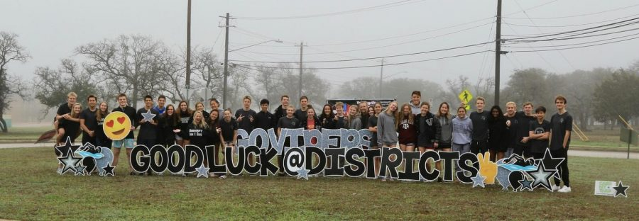 The swim team posing in front of their good luck sign after districts.