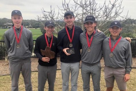 Boys golf players stand with awards and medals after tournament.