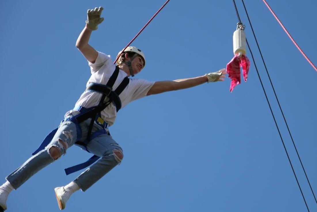 Senior Micheal Parrington takes a leap of faith on the high ropes to catch the bandana