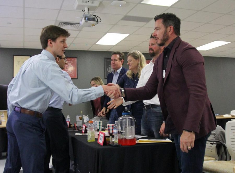 After presenting with his team, senior Jack Conlon shakes hands with real estate agent Gene Arant.
