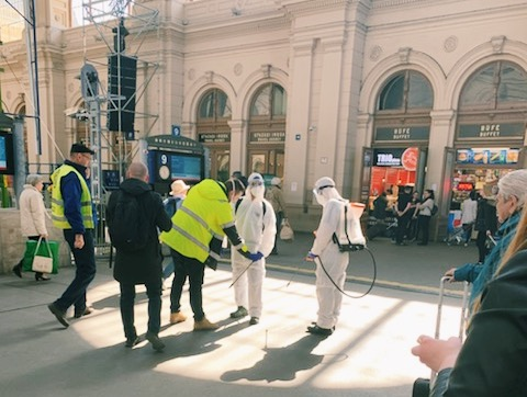 Student's godmother watches officials clean a train station in Budapest earlier in the week.