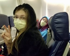 A student and her friend sit side-by-side on an airplane wearing surgical masks.