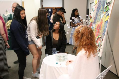 IB students interact with the audience during their art exhibition.