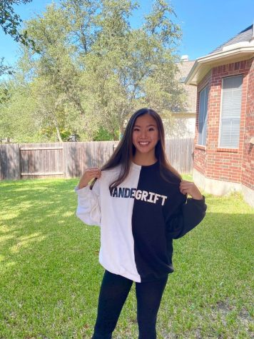 Natalie Wong smiles, as she models her new Vandegrift sweatshirt