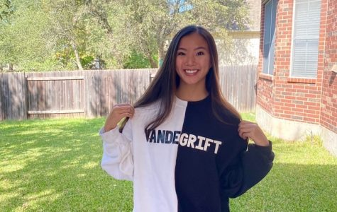 Natalie Wong smiles, as she models her new Vandegrift sweatshirt