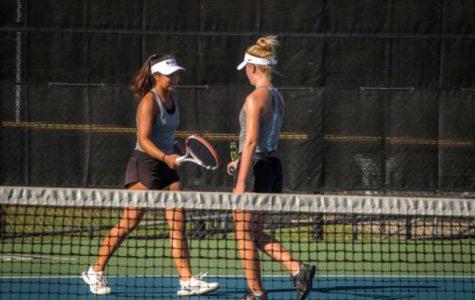 Hitting her racket against her partner freshman Lauren Tin's, sophomore Brooke Childress celebrates a point.