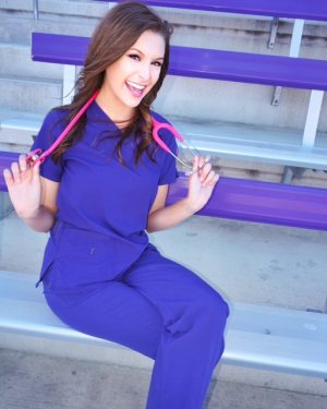 Hayley Walz poses and smiles in her nursing gear after her college graduation