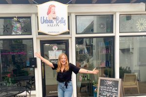 Vandegrift alumna and hairstylist Julie Latimer poses in front of Urban Betty.