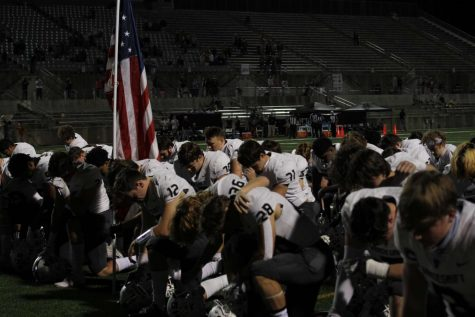 "The Vipers kneel at the end zone as senior captain Ryan Back prays with his team before the game begins. Back, number 12, is the team's quarterback and prioritizes praying before every game as the intensity builds up. ""In the football program we emphasize more than just football, but the development of our character as young men,"" Back said. ""Football has taught me discipline, teamwork. and leadership. I'm motivated to play and get better each week as I know my teammates are counting on me."""