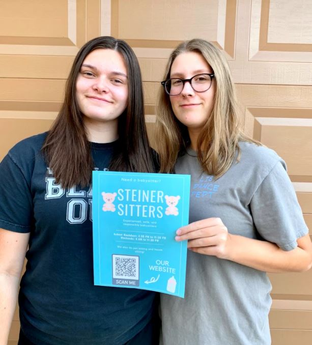 Founder Kira Anderson and Co-founder Shelby Thickstun holding a flyer for their recently launched buisness: Steiner Sitters