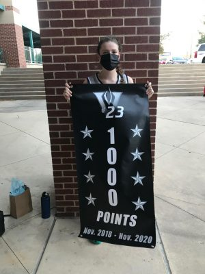 O'Rourke shows off banner to celebrate her accomplishment of scoring 1,000 points during her time on the team.
