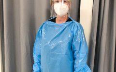 Vandegrift school nurse Jamie Ennis poses in her office wearing all of her protective gear.