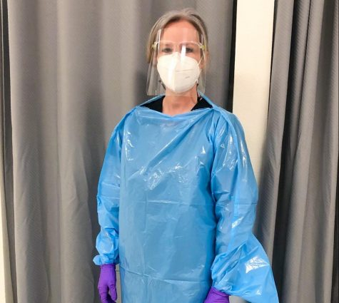 Vandegrift school nurse Jamie Ennis poses in her office wearing all of her protective gear.