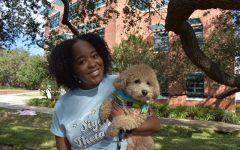 Kelli Steward stands outside the Sigma Theta Tau house at Trinity, wearing her Sigma Theta Tau shirt and holding a dog