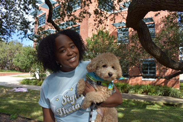 Kelli Steward stands outside the Sigma Theta Tau house at Trinity, wearing her Sigma Theta Tau shirt and holding a dog