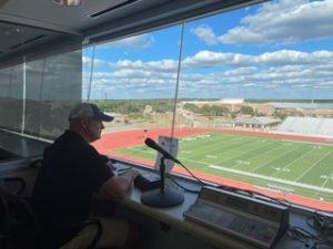 Brad Stanton sits in the sound booth, practicing and preparing for when he announces at the varsity football games
